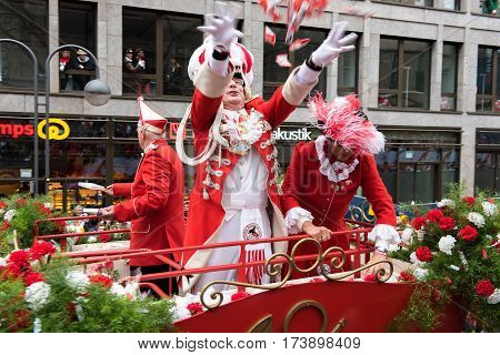 carnevalists on a parade vehicle giving away flowers - carnival in cologne - Participants of the rose monday parade in cologne on February 27, 2017