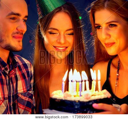 Happy friends birthday party with candle celebration cakes. People looking at burning candles. Two women and man have fun.