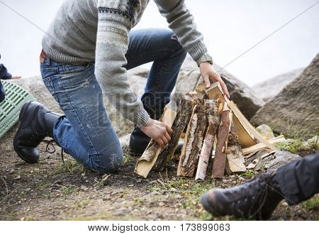 Man Arranging Firewood For Bonfire On Lakeside Camping