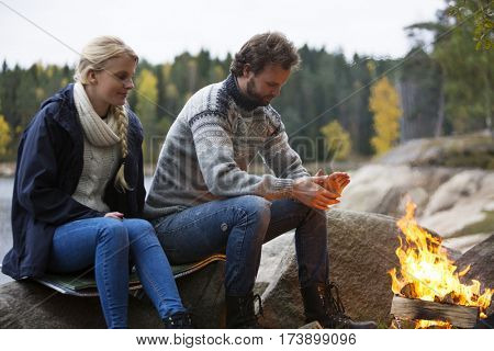 Couple Warming Themselves By Bonfire