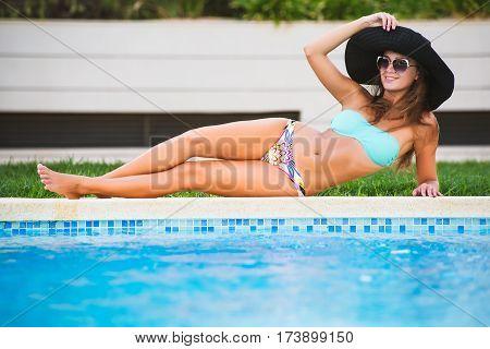 Beautiful Tanned Sexy Girl In Bikini And Black Hat Posing At A Swimming Pool