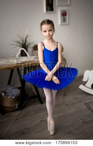 Child girl in a blue tutu dancing in a room.
