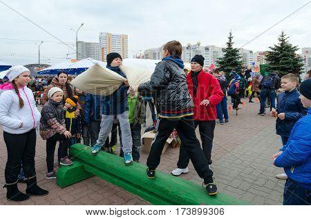 GOMEL BELARUS - MARCH 12 2016: Shrovetide entertainment. Unidentified children participate in funny battles on pillows