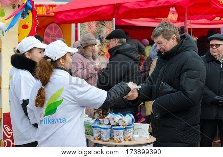 GOMEL BELARUS - FEBRUARY 21 2015: Young girls-sellers offer tasting of dairy products at fair during mass Shrovetide festivities