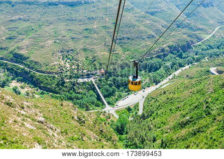 Panoramic views of the valley from the mountains of Montserrat. Near Barcelona, Spain. Beautiful nature in shades of green on a background of blue sky. Yellow cablecar cabin, cableway