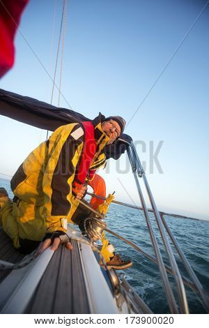 Man Cranking A Winch On Yacht In Sea