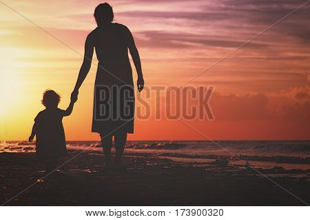 Silhouette of mother and little daughter walking on beach at sunset
