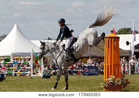 WEEDON, UK - SEPTEMBER 1: A rider competing in the main show jumping event in the large display arena successfully jumps a large fence at the Bucks County Show on September 1, 2016 in Weedon