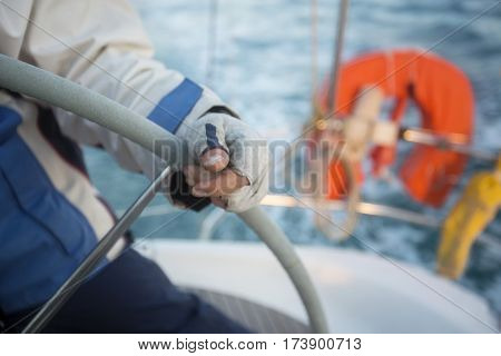 Midsection Of Man Steering Yacht