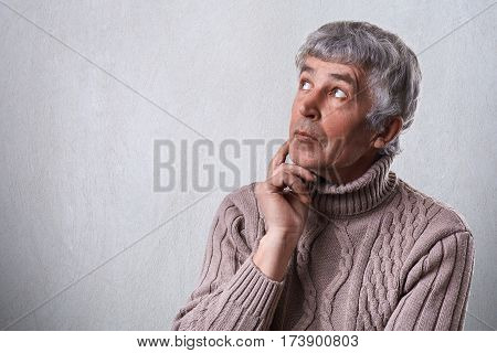 A close-up of dreamy elderly male holding his hand under chin looking aside having thoughtful faraway expression. Mature man daydreaming about something that makes him happy. Good memories