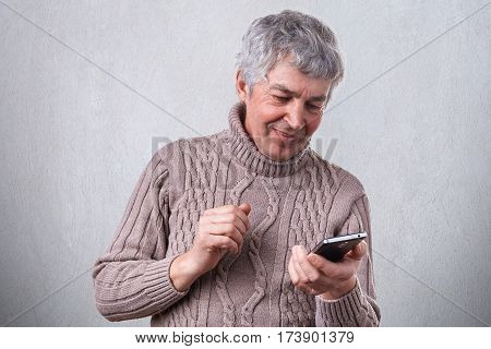 A happy smiling mature man holding his smartphone in hands being pleased to recieve message from his son. Technology people lifestyle and communication concept. Happy senior man having video call