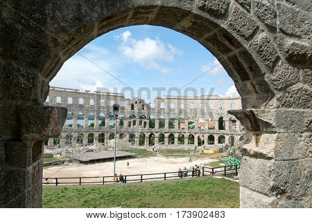Tourists Walking On The Ruins Of Roman Amphitheatre At Pula