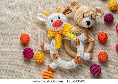 educational concept of sand pit bulls and bears in the financial market. crocheted rattle cow and bear children's toys among colorful beads. copy cpace for your text.