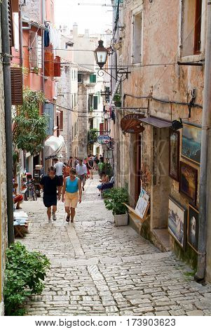 People Walking In The Narrow Alley Of Rovinj
