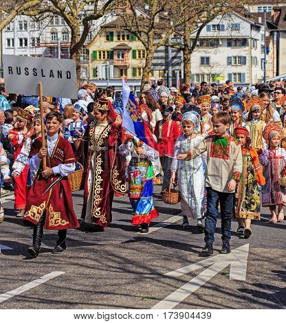 Zurich, Switzerland - 12 April, 2015: participants of children's parade devoted to the upcoming Sechselauten holiday passing along Uraniastrasse street. The Sechselauten is a traditional spring holiday in the city of Zurich, children's parade.