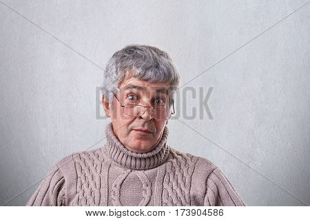 A close-up of surprised elderly man with gray hair and wrinkles wearing eyeglasses looking with wide open eyes into camera. Astonished wise grandfather hearing some news. People and lifestyle concept