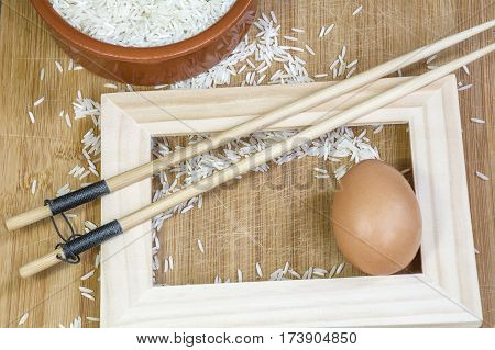 White basmati rice in clay bowl, chopsticks and frame on the light wooden background