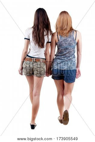 Back view going of two young woman brunette and blonde . Rear view people collection. backside view of person. beautiful girl friends walking. Isolated over white background.