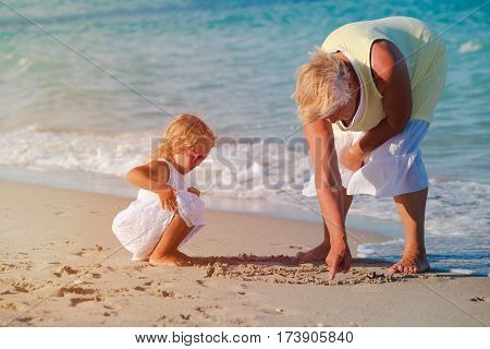 grandmother with little granddaughter play at tropical beach