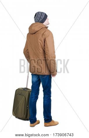 Back view of man in a brown jacket with  suitcase .   Standing young guy in jeans and  jacket. Rear view people collection.  backside view of person.  Isolated over white background.