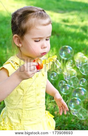 Cute little girl blowing soap bubbles on summer day outdoor