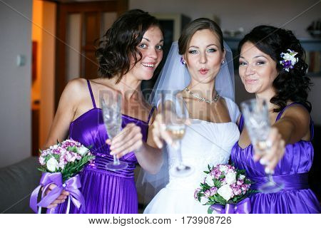 Bride and bridesmaids drink champagne during preparations
