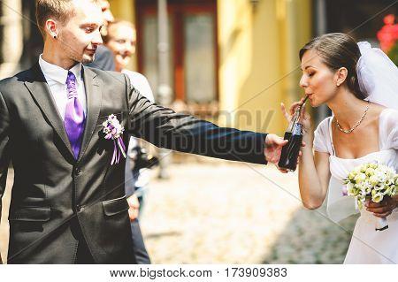 Bride drinks soda from a bottle held by groomsman
