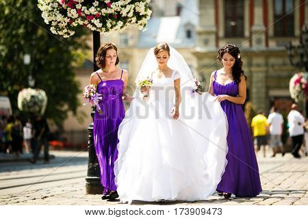 Bride walk together with bridesmaids along a blooming street