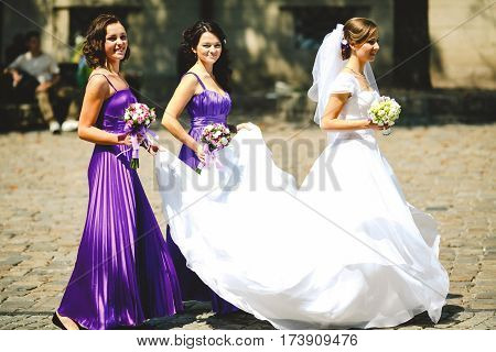 Bridesmaids in violet dresses hold bride's skirt while she walks along the street