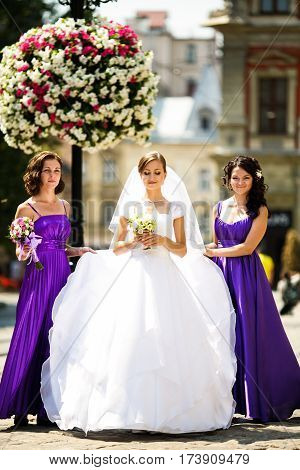 Bridesmaids in violet dresses surround a bride on the street