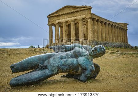 bronze statue of fallen ikaro on the background the concorde temple Agrigento Sicily Italy