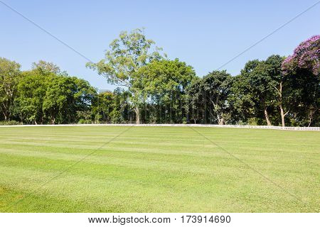 Cricket field grass outfield boundary fence grounds summer sport.