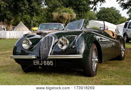 WESTERNHANGER, UK - JULY 17: A vintage Jaguar sports tourer motorcar stands on public display below the main racecourse tower at the War & Peace show on July 17, 2013 in Westernhanger
