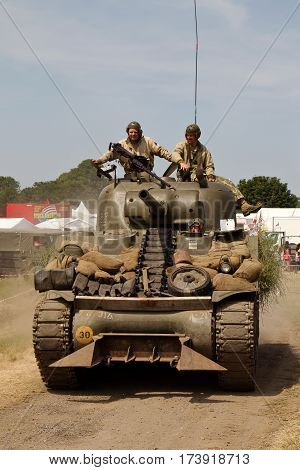 WESTERNHANGER, UK - JULY 17: Having done its display in the main arena a WW2 Sherman tank heads back to base in the Living History section at the War & Peace show on July 17, 2013 in Westernhanger
