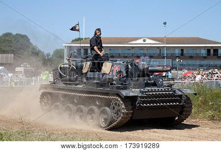 WESTERNHANGER, UK - JULY 19: Re-enactors ride their Panzer III tank around the arenas edge at the end of a battle re-enactment at the War & Peace show on July 19, 2013 in Westernhanger