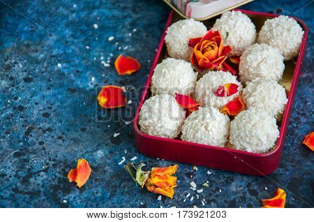 White chocolate truffles covered with coconut shavings in a small vintage metal box with rose petals on a blue background