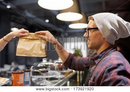 small business, people and service concept - man seller giving paper bag to customer at cafe