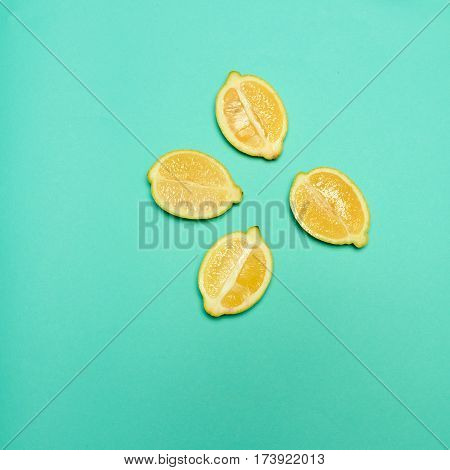 The fresh lemons cut in half on green background