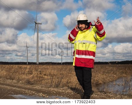 Confident Young Developer In A Nature Environment In Reflective Jacket And Safety Helmet, Talking By