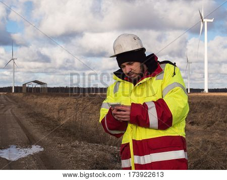 Portrait Of Young Engineer Working On Mobile Phone Outdoors In Helmet And Reflective Jacket