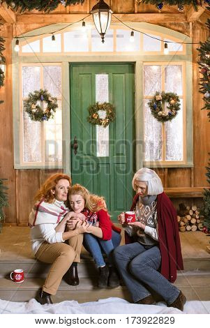 Family from three generations sitting on stairs while drinking hot tea