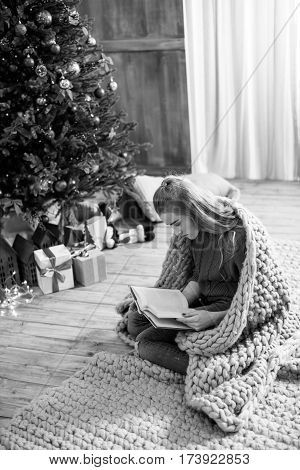 Thoughtful young woman sitting on carpet and reading book at christmastime black and white photo