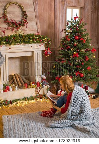 Thoughtful young woman sitting on carpet and reading book at christmastime
