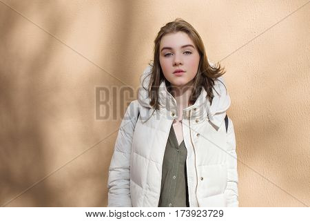Cold season young beautiful naughty woman in white coat posing against textured wall with light shadow pattern lifestyle concept portrait