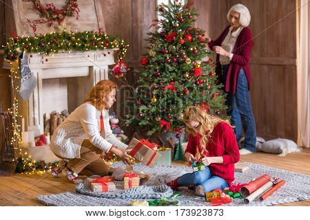 Three-generation family wrapping gift boxes and decorating christmas tree