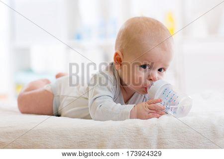 sweet baby boy holding bottle and drinking water in nursery