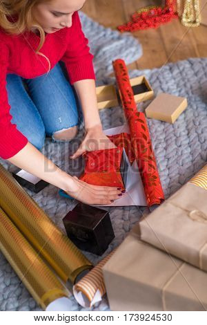 Partial view of girl sitting on floor with rolls of wrapping paper and wrapping gift boxes at christmastime