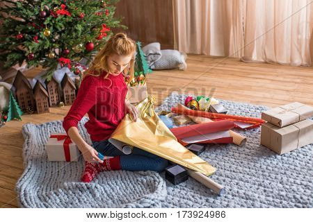 Blonde girl sitting on floor with rolls of wrapping paper and wrapping gift boxes at christmastime