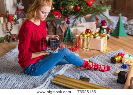 Blonde girl sitting on grey carpet and wrapping gift box at christmastime