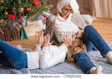 Teenage girl lying on the knees of her grandmother and chatting near the Christmas tree
